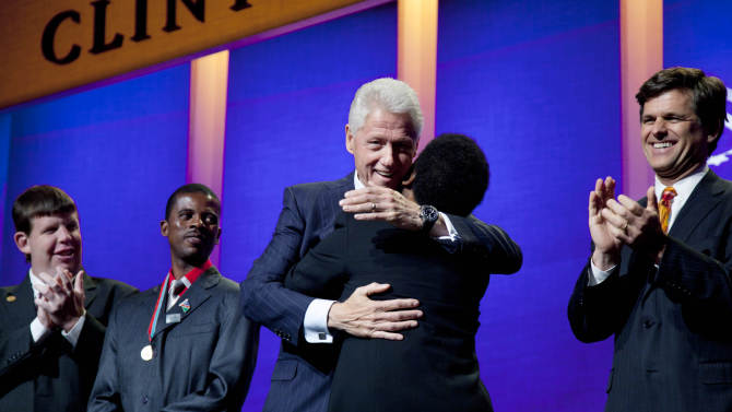 Former U.S. President Bill Clinton hugs Special Olympics athlete Loretta Claiborne after she addressed the opening session of the Clinton Global Initiative, Sunday, Sept. 23, 2012, in New York. From left are athletes Dustin Plunkett and Deon Namiseb. Tim Shriver, CEO of the Special Olympics, is at right. (AP Photo/Mark Lennihan)