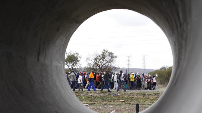 Striking platinum miners take part in a march to the Rustenburg, South Africa, police station, Sunday, Sept. 16, 2012 to protest the heavy handed way the police are cracking down on strikers who have been off work since early last month. The march was declared illegal by the police, who prevented the protesters from entering the town, and the strikers dispersed peacefully. (AP Photo/Denis Farrell)