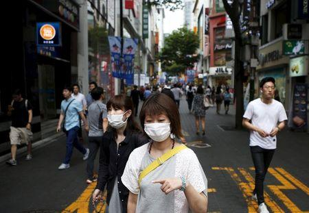 Women wearing masks to prevent contracting Middle East Respiratory Syndrome (MERS) walk at Myeongdong shopping district in central Seoul