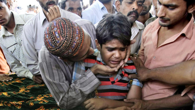 A Pakistani boy is comforted by a relative during the funeral procession of his brother, who was killed in a Bhoja Air  Boeing 737 plane that crashed on the outskirts of Islamabad on Friday killing all 127 people on board, in Karachi, Pakistan, Sunday, April 22, 2012. Pakistan has barred the head of the airline whose jet crashed near the capital from leaving the country, vowing to investigate a tragedy that has revived fears about the safety of aviation in a country saddled by massive economic problems. (AP Photo)