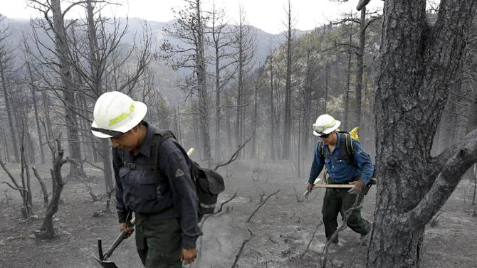 """Members of Bighorn 209, a hand crew from the Crow Agency in Montana check for hot spots on the Waldo Canyon Fire west of Colorado Springs, Colo., Friday, June 29, 2012. After declaring a """"major disaster"""" in the state early Friday and promising federal aid, President Barack Obama got a firsthand view of the wildfires and their toll on residential communities. More than 30,000 people have been evacuated in what is now the most destructive wildfire in state history. (AP Photo/Chris Carlson)"""