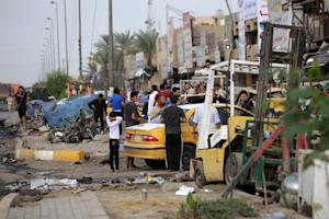Iraqis inspect the site of a suicide car bomb attack…
