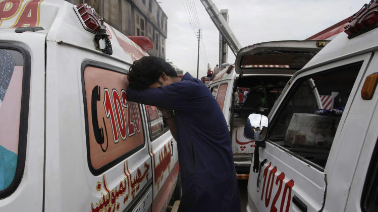 A Pakistani weeps beside the ambulances parked at the site of burnt garment factory in Karachi, Pakistan on Wednesday, Sept. 12, 2012. Pakistani officials said the death toll from devastating factory fires that broke out in two major cities has risen to 128. (AP Photo/Fareed Khan)