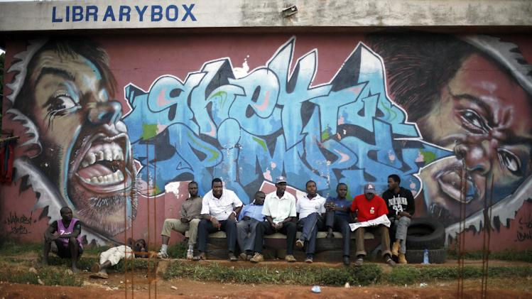 "Kenyan men sit in the Kibera Slum of Nairobi, Kenya, Sunday March 10, 2013, under a graffiti artwork with the slogan ""Ghetto Pimps"", one day after Uhuru Kenyatta was declared winner in the Kenyan presidential elections Kenya's election commission posted complete results early Saturday showing that Deputy Prime Minister Uhuru Kenyatta prevailed in the country's presidential elections by the slimmest of margins, winning 50.03 percent of the vote. (AP Photo/Jerome Delay)"