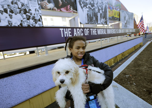 "Arianna Dorman of Fort Washington, Md., holds her dog ""Luke,"" as she poses for a picture with the civil rights movement float prepared for the 57th Presidential Inaugural Parade, Sunday, Jan. 20, 2013"