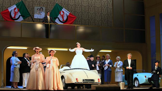 """FILE - In this Jan. 22, 2013 file photo singers perform during a dress rehearsal for the opera """"La Cenerentola"""" by Gioachino Rossini, at the state opera in Vienna, Austria. There is no pumpkin-turned-coach on the stage, no glass slipper, no fairy godmother, and the action takes place in an imaginary Italian duchy in the 1950s. But Gioachino Rossini's take on Cinderella remains utterly magical in the new version being put on by the Vienna State Opera with the premiere on Sunday Jan. 27, 2013. (AP Photo/dapd, Lilli Strauss)"""