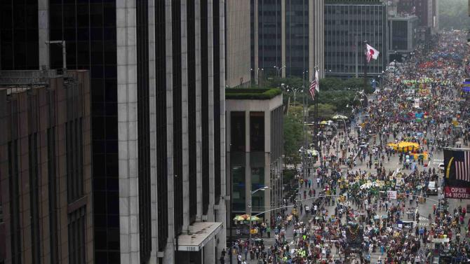 Thousands march down 6th Avenue while taking part in the People's Climate March through Midtown, New York