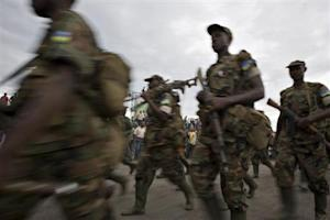 Rwandan soldiers march past a crowd gathered to watch thousands of Rwandan  troops returning home across the border at Goma