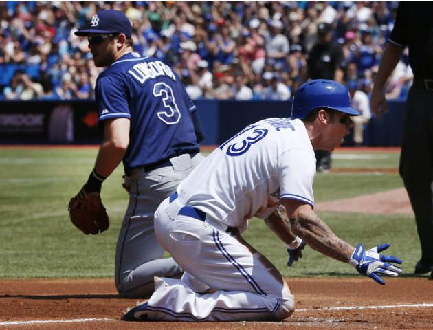 Jays' Lawrie celebrates his RBI triple against Rays third baseman Evan Longoria during the first inning of their MLB American League baseball game in Toronto