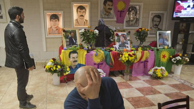 Kurds mourn next to a table cover by flowers and pictures of the three Kurdish activist killed Thursday in the French capital and their leader Abdullah Ocalan in Paris, Friday, Jan. 11, 2013. Turkey's prime minister suggested Friday that a feud among Kurdish rebels was behind the shooting deaths of three Kurdish activists in Paris, and the rebels said it was an attempt to undermine peace talks that their jailed leader is holding with Turkey. (AP Photo/Michel Euler)