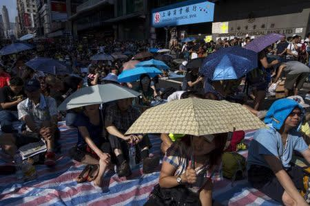 Protesters sit under umbrellas at a main street at Mongkok shopping district after thousand of protesters blocked the road in Hong Kong