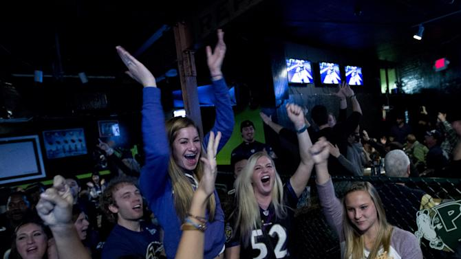 Baltimore Ravens fans cheers for their team after they scored the first touchdown against San Francisco 49ers, as they watch the game at local pub in Baltimore Md. on Sunday Feb. 3, 2013. (AP Photo/Jose Luis Magana)