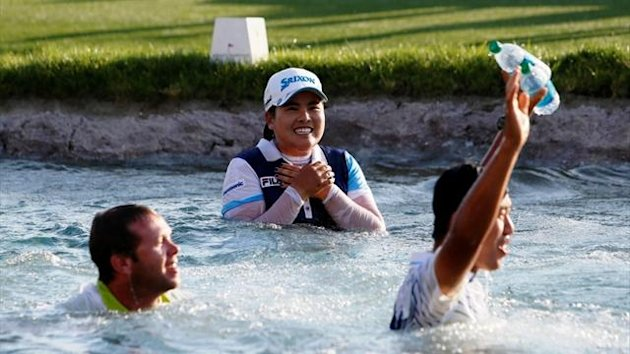 Inbee Park (centre) of South Korea laughs with her caddie Brad Beecher (left) and her fiance Gi Hyeob Nam (right) after jumping into Poppie's Pond surrounding the 18th green to celebrate winning the Kraft Nabisco Championship in California (Reuters)
