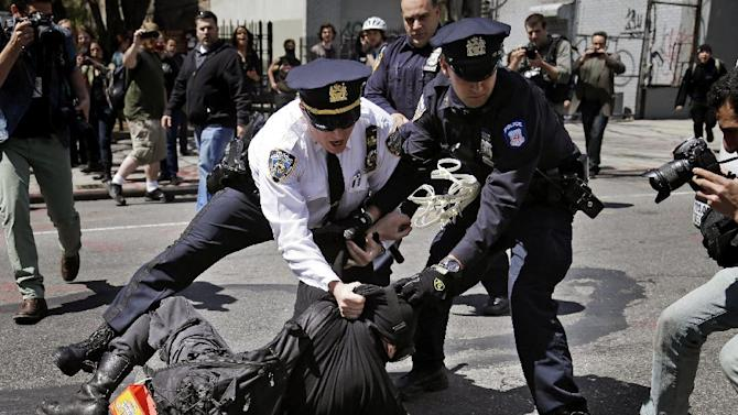 Police officers work to restrain a protester during May Day rallies in New York, Wednesday, May 1, 2013. Activists in New York City are protesting working conditions, immigration reform and other issues. (AP Photo/Seth Wenig)