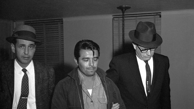 """FILE - In this Jan. 6, 1960 file photo, Perry Edward Smith is led by police officers into the courthouse at Garden City, Kan. Smith was arrested in Las Vegas and charged with first degree murder in the slaying of four members of the Herbert Clutter family at their farm house in Holcomb, Kan. Fifty years ago, the Clutter murders inspired Truman Capote to write """"In Cold Blood"""".  A Florida detective wants to exhume the bodies of Edward Smith and accomplice Richard Hickock to see if there is evidence linking the two men to the 1959 murders of four in a rural community south of Sarasota. (AP Photo/William Straeter, FILE)"""