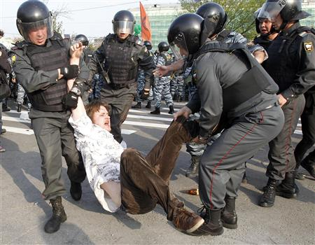Russian riot police detain a participant during a &quot;march of the million&quot; opposition protest in central Moscow