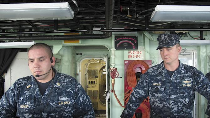 Navy Chief Petty Officer Eleuterio Roman, left, and Lt. Steve Hartley, monitor screens on board the USS Freedom as it nears Pearl Harbor, Hawaii, Monday, March 11, 2013. The USS Freedom, which is stopping in Hawaii on its way to a deployment to Singapore, has advantages its bigger siblings lack. It is small enough to move among the many islands and shallow waters lining the extensive coastlines of Southeast Asia.  (AP Photo/Audrey McAvoy)