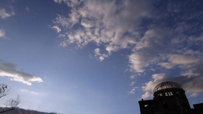 The sun sets by the gutted Atomic Bomb Dome, right, in Hiroshima, western Japan, Saturday, Aug. 4, 2012. Hiroshima marks the 67th anniversary of the atomic bombing on Aug. 6. (AP Photo/Itsuo Inouye)