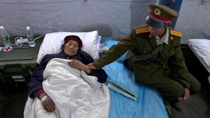 A Chinese soldier looks after an elderly relative resting in a military field hospital in the county seat of Lushan in Sichuan province, China, Monday, April 22, 2013. The efforts under way in the mountainous province after a quake Saturday that killed nearly 200 people showed that the government has continued to hone its disaster reaction — long considered a crucial leadership test in China — since a much more devastating earthquake in 2008, also in Sichuan, and another one in 2010 in the western region of Yushu. (AP Photo/Ng Han Guan)