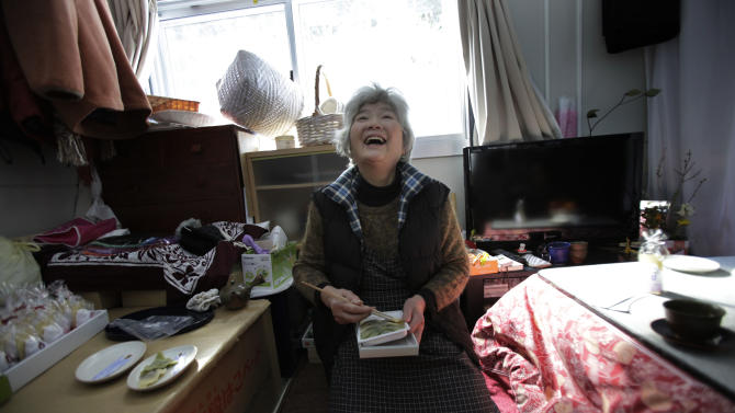 In this Saturday, Feb. 23, 2013 photo,  Hide Sato, 83, who survived the March 11, 2011 earthquake and tsunami smiles as she sits inside her room at a temporary housing complex in Rikuzentakata, Iwate Prefecture, northeastern Japan. Like tens of thousands of other Japanese who lost everything in the tsunami that pulverized much of Japan's northeastern coast in March 2011, Sato is living in one-room temporary housing, and longing for a home of her own. (AP Photo/Junji Kurokawa)