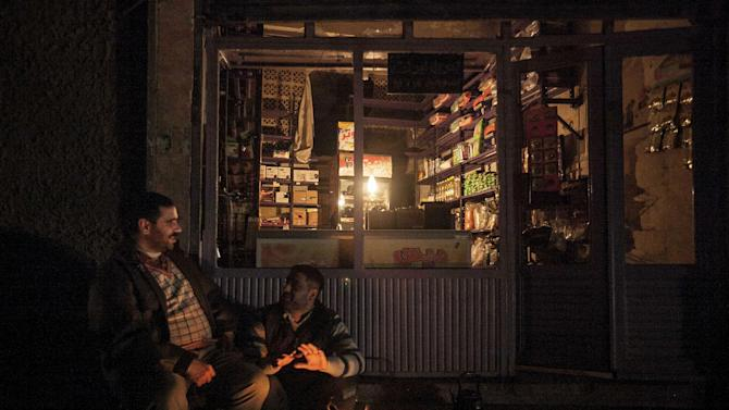 In this Thursday, Nov. 29, 2012 photo, night falls as men warm themselves by a fire in a Syrian rebel controlled area in where residents are trying to get back to their daily lives after months of heavy fighting in Aleppo, Syria. (AP Photo/Narciso Contreras)