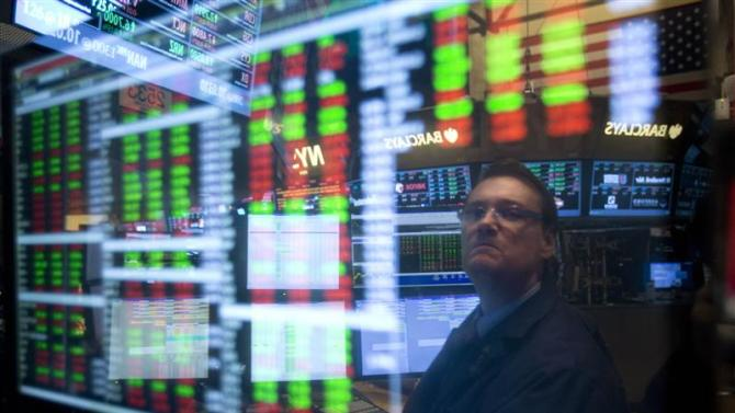 Trader is reflected in a screen as he works on the floor of the New York Stock exchange in New York