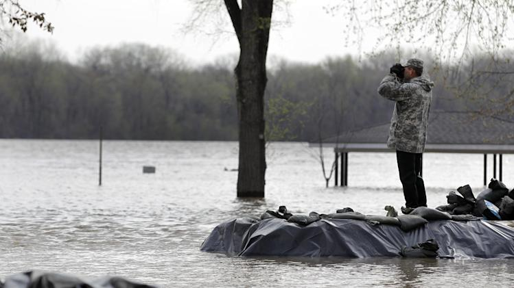 A member of the Missouri National Guard stands on a sandbag levee and looks out over floodwater from the Mississippi River, Sunday, April 21, 2013, in Clarksville, Mo. Many have come to the aid of the tiny community, working since Wednesday to build a makeshift sandbag levee that seemed to be holding as the crest, expected to be 11 feet above flood stage, approaches. (AP Photo/Jeff Roberson)
