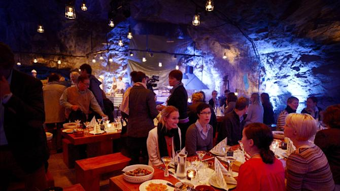 """Customers having dinner at Muru Pop Down -restaurant at Tytyri mine in Lohja, Finland on Monday Sept. 10 2012. The award-winning chef, Niklas Ekblom, is opening a new restaurant in Finland that turns the idea of """"pop-up"""" eateries upside-down: it's located 80 meters (260 feet) underground. Discerning food lovers are being served salted salmon, veal tenderloin snails cooked in Pernod, and apple crumble in the """"pop-down"""" restaurant in a limestone mine in the small, southern town of Lohja, 60 kilometers (40 miles) west of Helsinki. A four-course evening meal costs 128 euro ($160), including drinks and transportation down to the mine and back up. (AP Photo/Lehtikuva, Antti Aimo-Koivisto)  FINLAND OUT"""
