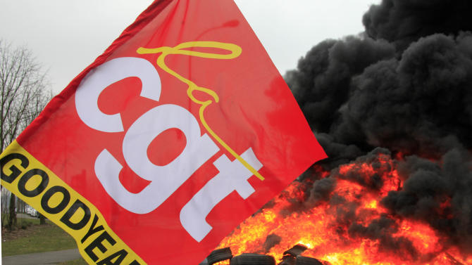 The flag of the CGT union (General Confederation of Work), is seen around burning tires, outside the Goodyear tire company, in Amiens, northern France, Tuesday Feb. 26, 2013. Workers at a dying French tire factory who've become the butt of American jokes are staging a day of last-ditch protests to try to save their jobs. The protests in the northern city of Amiens come after efforts to find a new buyer for the struggling plant have fizzled. An American executive who considered buying it sent a letter last week to the French government saying that France's economic model is too worker-friendly and discourages investment.   (AP Photo/Michel Spingler)