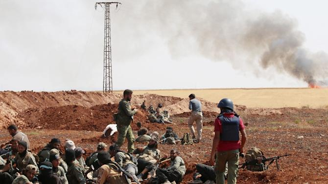 An unidentified photographer (R) stands next to rebel fighters from Jaysh al-Islam (Army of Islam) holding a position behind a sand barrier on the frontline in the Bashkoy area, on the northern outskirts of Aleppo, northern Syria on August 25, 2015