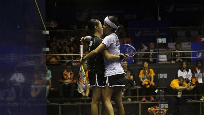 Malaysia's Nicol David hugs with her compatriot Low Wee  after their women's single squash match final at the 17th Asian Games in Incheon