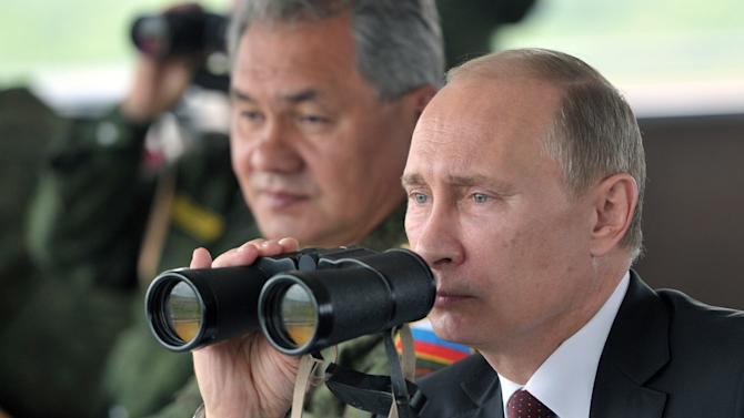 Russian President Vladimir Putin uses binocular as he watches military exercise near Yuzhno-Sakhalinsk, on Sakhalin Island on Tuesday, July 16, 2013. The maneuvers in Siberia and the far eastern region involved 160,000 troops and about 5,000 tanks - a massive show of force unprecedented since the Soviet times. Defense Minister Sergei Shoigu sits at left. (AP Photo/RIA Novosti, Alexei Nikolsky, Presidential Press Service, Pool)