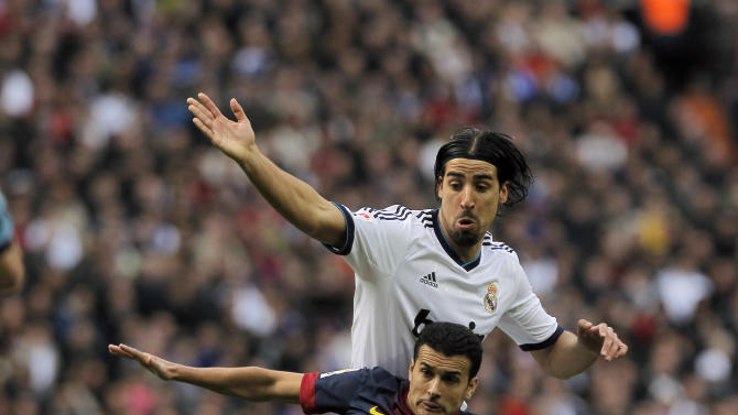 Real Madrid's Sami Khedira from Germany, top, in action with FC Barcelona's Pedro Rodriguez during a Spanish La Liga soccer match at the Santiago Bernabeu stadium in Madrid, Spain, Saturday, March 2, 2013. (AP Photo/Andres Kudacki)