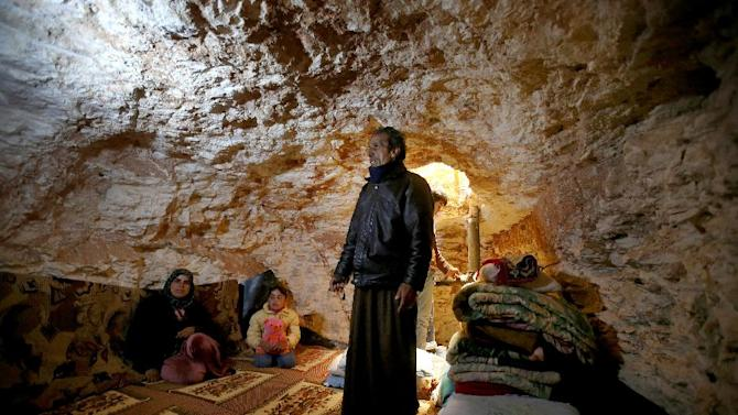 AP10ThingsToSee - Sobhi al-Hamod, 60, stands inside an underground shelter he made to protect his family from the Syrian government's shelling and airstrikes, at Jirjanaz village, in Idlib province, Syria, Thursday, Feb. 28, 2013. Across northern Syria, rebels, soldiers, and civilians are making use of the country's wealth of ancient and medieval antiquities to protect themselves from Syria's two-year-old war. (AP Photo/Hussein Malla, File)