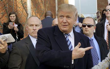 U.S. Republican presidential candidate Donald Trump points at a supporter at a polling place for the presidential primary in Manchester