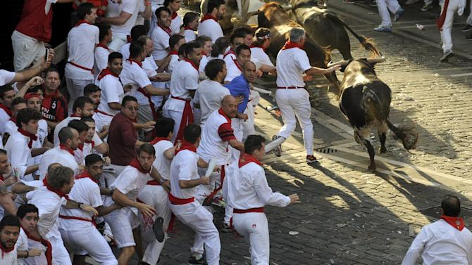 Runners sprint alongside Jandilla fighting bulls at the town hall square during the first running of the bulls of the San Fermin festival in Pamplona