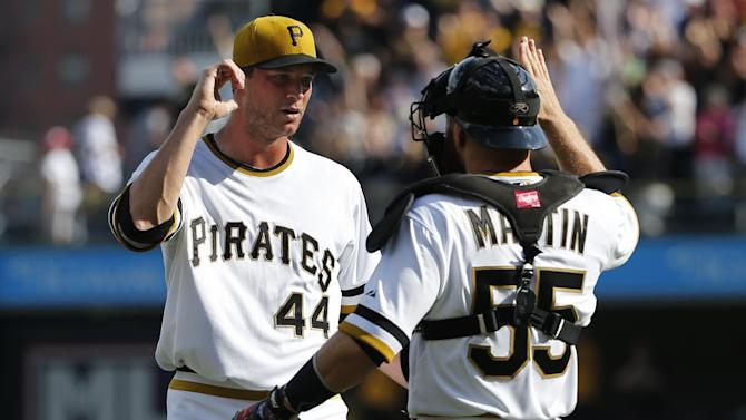 Pittsburgh Pirates relief pitcher Tony Watson (44) celebrates with catcher Russell Martin (55) after getting the final out of the ninth inning during a baseball game against the Milwaukee Brewers in Pittsburgh Sunday, Sept. 21, 2014. The Pirates won 1-0. (AP Photo/Gene J. Puskar)