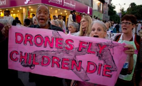 """American citizens hold a banner that reads """"Drones fly children die"""" during an anti-war rally in Pakistan on Oct. 5, 2012."""