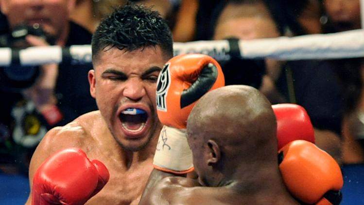 In this photo provided by the Las Vegas News Bureau, Victor Ortiz, left, battles Floyd Mayweather for the WBC welterweight championship boxing title, Saturday, Sept. 17, 2011, in Las Vegas. (AP Photo/Las Vegas News Bureau, Brian Jones)