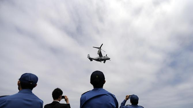 A Marine MV-22 Osprey aircraft takes off as sailors and a journalist take pictures aboard the the Japanese destroyer JS Hyuga Friday, June 14, 2013, in coastal waters off San Diego. The aircraft made an unprecedented landing on the vessel Friday, despite protests in Japan over concerns over the tilt-rotor aircraft's safety record. (AP Photo/Gregory Bull)