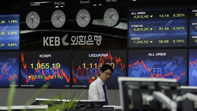 A currency trader walks by near a screens at the foreign exchange dealing room of the Korea Exchange Bank headquarters in Seoul, South Korea, Wednesday, Oct. 10, 2012. Worries about Europe's debt crisis, signs of weak global growth and expectations of lower U.S. corporate earnings sent Asian stocks down on Wednesday. South Korea's Kospi lost 1 percent at 1,958.41. (AP Photo/Lee Jin-man)