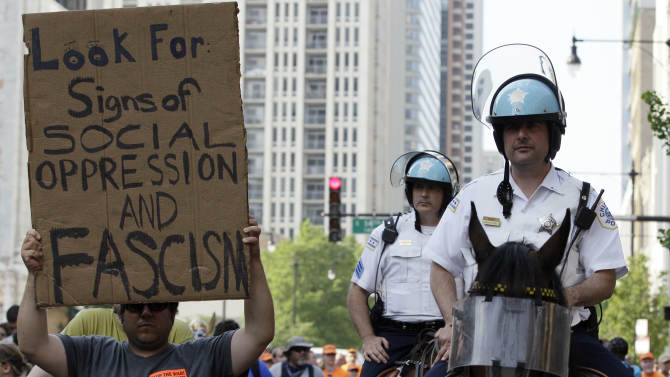 A protester marches next Chicago police mounted patrols on Michigan Avenue during a NATO summit demonstration in Chicago, Saturday, May 19, 2012. Security has been high throughout the city in preparation for the summit, where delegations from about 60 countries will discuss the war in Afghanistan and European missile defense. (AP Photo/ Nam Y. Huh)