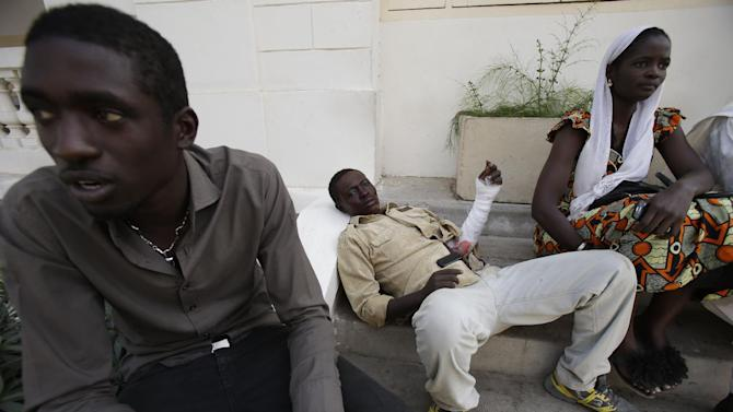 University student Mansour Niang, 27, center, who set himself on fire to protest grading changes that would keep him from continuing his studies, rests with fellow students on steps outside the entrance to the emergency ward, after being treated for burns on his arm and face at the main municipal hospital, in Dakar, Senegal Friday, March 15, 2013. Niang and two other students who tried to immolate themselves Friday are part of a group of 50 geography majors who say a new grading system has unfairly left them one credit short of receiving their diplomas, and will block them from continuing to their fourth-year masters degree at the public university. Student witnesses said students unconnected to the protest immediately threw sand on Niang to put out the fire and stopped the two other students from setting themselves alight. (AP Photo/Rebecca Blackwell)