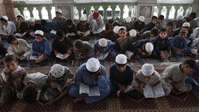 Afghan boys read the Quran during the Muslim holy month of Ramadan at a mosque in the city of Jalalabad, the provincial capital of Nangarhar province, east of Kabul, Afghanistan, Sunday, July 22, 2011. Muslims from Morocco to Afghanistan are experiencing the toughest Ramadan in more than three decades with no food or drink, not even a sip of water, for 14 hours a day during the hottest time of the year. (AP Photo/ Rahmat Gul)