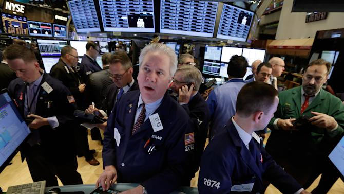 FILE - In this Wednesday, March 5, 2014, file photo, specialist Brian Egan, foreground left, works on the floor of the New York Stock Exchange. A surging stock market and rebounding home prices boosted Americans' wealth to a record in the final three months of last year, though both trends have slowed so far in 2014. (AP Photo/Richard Drew, File)
