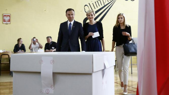 Duda, presidential candidate of the Law and Justice Party (PiS), walks to a ballot box to cast his vote next to his wife Agata and their daughter Kinga in a polling station in Krakow