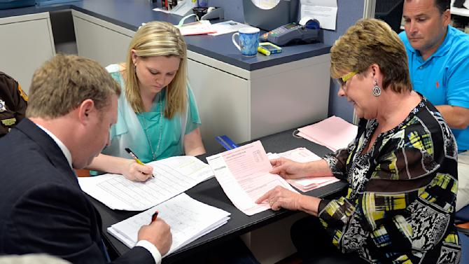 Ohio County Clerk Bess Ralph, left, shows vote totals to James Comer representative Darren Embry, right, as Assistant County Clerk Chelsea Rusher records the count during the recanvass of the Kentucky Republican Gubernatorial primary race, Thursday May 28, 2015, in Hartford Ky. (AP Photo/Timothy D. Easley)