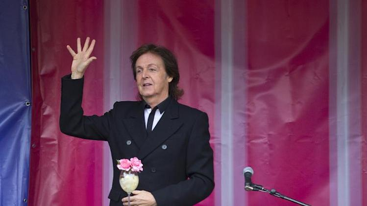 Former Beatle Paul McCartney waves to the crowd following an impromptu gig in Covent Garden in London on October 18, 2013