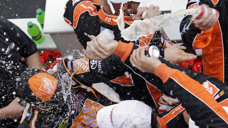 Joey Logano, left, is celebrates with crew members after winning NASCAR's Sprint Cup Series Pocono 400 auto race on Sunday, June 10, 2012, in Long Pond, Pa. (AP Photo/Matt Slocum)