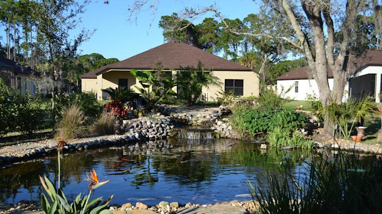 This undated photo provided by Kristen Alligood shows a pond designed by Sonny Alansky for the backyard of his home in Rockledge, Fla. It measures roughly 37 feet in diameter, has three waterfalls and 14 koi fish. Backyard ponds, which range from small and simple to meandering and ornate, can become a passion for many gardeners. (AP Photo/Kristen Alligood)